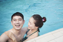 Happy couple smiling and relaxing in the pool Stock Images