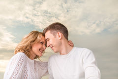 Happy couple smiling and watching one another under the sunny sk Royalty Free Stock Images