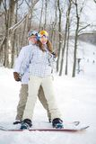Happy couple of snowboarders Stock Photos