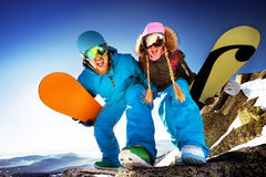 Happy couple of snowboarders stands on big rock. Mountains backdrop Royalty Free Stock Image