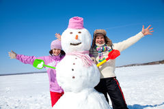 Happy couple with snowman Royalty Free Stock Image