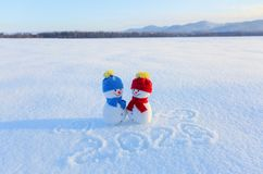 Happy couple of snowman in love standing on the snow. Writings 2019. Landscape with mountains in the cold winter day. royalty free stock images