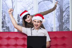 Happy couple on sofa with laptop in xmas day Stock Images