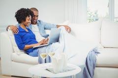 Happy couple on the sofa using laptop Stock Photo
