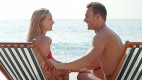 Happy couple speaking together and looking at each other. At the beach stock video