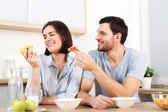 Happy couple spend free time or weekend together at kitchen, glad husband suggests wife to eat snack, she refuses as Stock Images