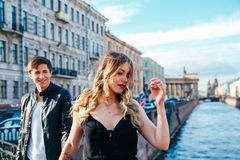 Happy couple is spending vacation holidays in St. Petersburg. Both look really happy. They are strolling along the streets of the Stock Photo