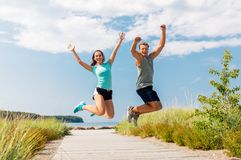 Happy couple in sports clothes jumping on beach Royalty Free Stock Photos