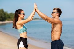 Happy couple in sports clothes and shades on beach Royalty Free Stock Photography