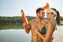 Happy couple with squirt guns at a lake Stock Images