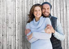 Happy couple standing against wooden background Stock Photo