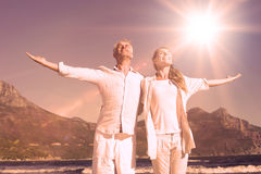Happy couple standing with arms outstretched at the beach Stock Photography