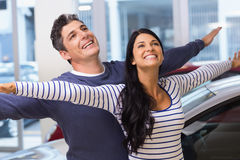 Happy couple standing with arms outstretched Royalty Free Stock Photo