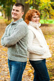 Happy couple standing back to back Royalty Free Stock Photos