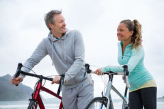 Happy couple standing with bicycle on beach Royalty Free Stock Images