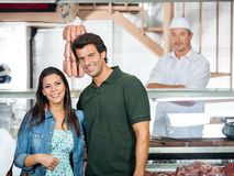 Happy Couple Standing In Butcher Shop Royalty Free Stock Image