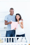 Happy couple standing by crib Royalty Free Stock Image