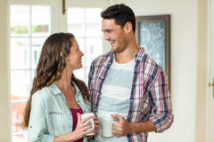 Happy couple standing with cup of tea Stock Photos