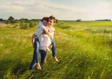 Happy couple standing in the field at the sunset Royalty Free Stock Photo