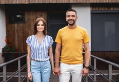 Happy couple standing in front of building stock photography