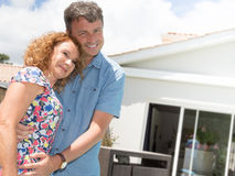 Happy couple standing in front of house under construction Royalty Free Stock Images
