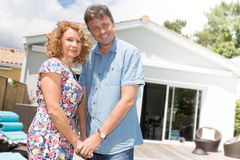 Happy couple standing in front of house under construction Stock Photo