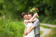 Happy couple standing in green park, kissing, smiling, laughing Royalty Free Stock Image