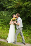 Happy couple standing in green park, kissing, smiling, laughing Royalty Free Stock Photos
