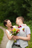 Happy couple standing in green park, kissing, smiling, laughing Royalty Free Stock Images