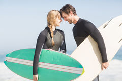 Happy couple standing head to head with surfboard Royalty Free Stock Images