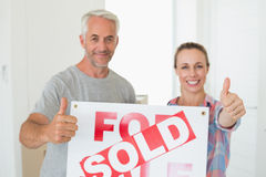 Happy couple standing and holding sold sign giving thumbs up Royalty Free Stock Photography
