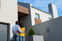 Happy couple standing and looking at the new house stock photos