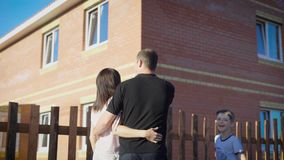 Happy couple standing outside embracing and looking at new fenced apartment. Loving family in summer sunny day showing stock video footage