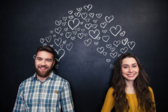 Happy couple standing over background of chalkboard with drawn hearts Stock Image