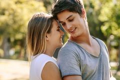 Happy couple standing in park together stock image