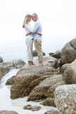 Happy couple standing on the rock and looking at each other Stock Image