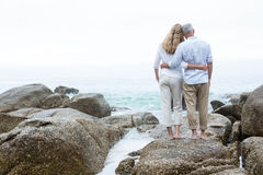 Happy couple standing on the rock and looking at the sea Stock Photo