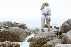 Happy couple standing on the rock and looking at the sea Stock Photography
