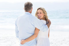 Happy couple standing by the sea arms around Stock Photography