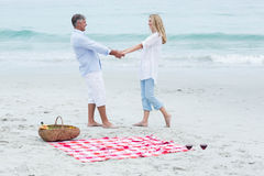 Happy couple standing by the sea and holding hands Stock Images
