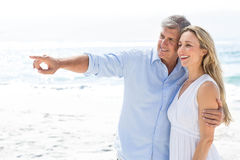 Happy couple standing by the sea and pointing something Stock Photo
