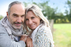 Happy couple standing together in countryside Royalty Free Stock Image