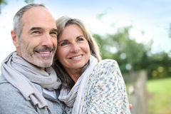Happy couple standing together in fields royalty free stock photo