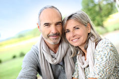 Happy couple standing together in fields Stock Photo