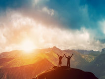 A happy couple standing together on a mountain. A happy couple standing together on the peak of a mountain with hands raised admiring breathtaking view at sunset Stock Photos