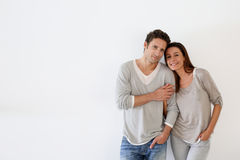 Happy couple standing together on white wall Stock Photo