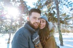 Happy couple standing in winter park Stock Photos
