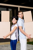 Happy couple stands back to back with boxes Stock Photography