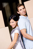 Happy couple stands back to back with containers Royalty Free Stock Photo