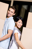Happy couple stands back to back with packages Royalty Free Stock Image